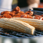 Corncobs and meat on grill --- Image by © Royalty-Free/Corbis